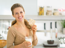 Happy young woman having snacks in kitchen Royalty Free Stock Image