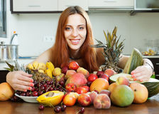 Happy young woman with heap of fruits Royalty Free Stock Image
