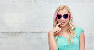 Happy young woman in heart shape sunglasses Stock Images
