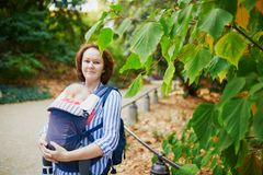 Happy young woman with her baby in carrier stock photography