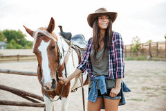 Happy young woman with her horse at the farm Stock Photography