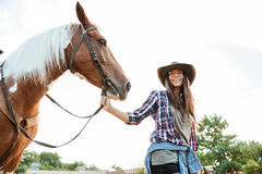 Happy young woman with her horse at the farm Royalty Free Stock Image