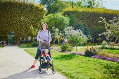 Happy young woman with her little baby girl in stroller stock image