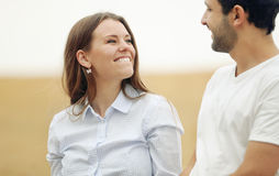 Happy young woman with her man walking together in summer field Stock Image