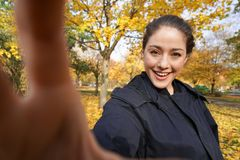 Happy young woman taking selfie photo in park with autumn colors. Happy young woman in her 20s taking selfie photo posing in park with autumn colors - wide angle stock images