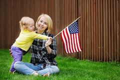 Happy young woman with her toddler girl holding american flag Royalty Free Stock Photo