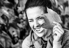 Happy young woman hiding behind autumn leafs in fron. T of foliage Stock Photos