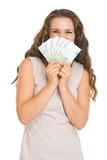 Happy young woman hiding behind fan of euros Stock Photo