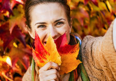 Happy young woman hiding behind leaf while making selfie in fron Stock Photography