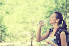 Happy young woman hiker with backpack drinking bottled water Stock Photos