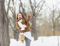 Happy young woman hitting snow with leg Royalty Free Stock Image