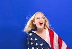Happy young woman holding an American flag stock photography