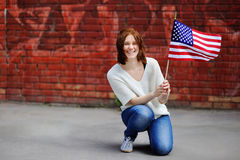 Happy young woman holding american flag Stock Image