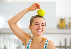 Happy young woman holding apple on head Stock Photography