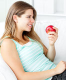Happy young woman holding an apple on a sofa. At home Stock Photography