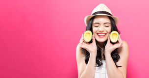 Happy young woman holding avocado halves Royalty Free Stock Image