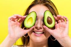 Happy young woman holding avocado halves Stock Photos