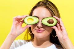 Happy young woman holding avocado halves Royalty Free Stock Photo