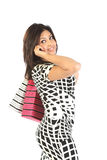 Happy young woman holding bags and talking by phone royalty free stock photos