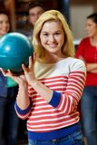 Happy young woman holding ball in bowling club Stock Images