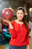 Happy young woman holding ball in bowling club Stock Image