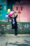 Happy young woman holding balloons jumping high royalty free stock photography