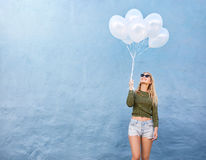 Happy young woman holding balloons Stock Photo