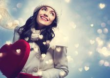 Young woman holding a big heart gift box Royalty Free Stock Images