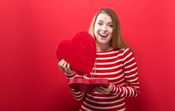 Happy young woman holding a big heart gift box stock images