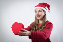 Happy young woman holding a big heart present for Cristmas day Royalty Free Stock Photo