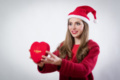 Happy young woman holding a big heart present for Cristmas day Stock Photos