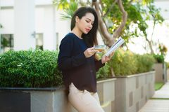 Happy young woman holding book fond of literature analyzing novel during leisure time on terrace of campus cafe in sunny day. royalty free stock photos