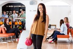 Happy Young Woman Holding Bowling Ball in Club. Portrait of happy young women holding bowling ball with people in background at club Royalty Free Stock Photo