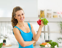Happy young woman holding bunch of radishes Stock Photos
