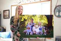Happy Young Woman Holding Canvas Print of Family Portrait royalty free stock photo