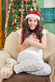 Happy young woman holding christmas present box wearing Santa hat Stock Photos