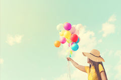 Happy young woman holding colorful balloons with floating Royalty Free Stock Photo