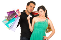 Happy young woman holding credit card while Royalty Free Stock Image