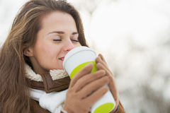 Happy young woman holding cup of hot beverage in winter outdoors Royalty Free Stock Photo