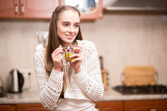 Happy young woman holding cup of tea at the kitchen Stock Photography