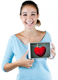 Happy young woman holding a digital tablet with a heart on the s Stock Photos
