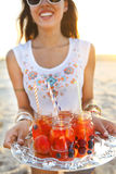 Happy young woman holding a dish with a drinks at summer party Royalty Free Stock Image