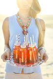 Happy young woman holding a dish with a drinks at sunset party Royalty Free Stock Photo