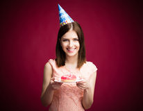 Happy young woman holding donut with candle Royalty Free Stock Photo