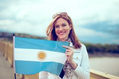 Happy young woman holding flag of Argentina on bridge royalty free stock photos