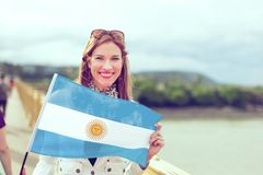 Happy young woman holding flag of Argentina graded. Happy young woman holding flag of Argentina with toothy smile, outdoors, color graded stock photography