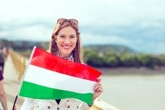 Happy young woman holding flag of Hungary outdoors, graded. Happy young woman holding flag of Hungary with toothy smile, outdoors, color graded royalty free stock photography