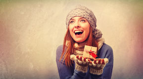 Happy young woman holding a gift box Stock Photography