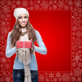 Happy young woman holding gift over winter background Royalty Free Stock Image