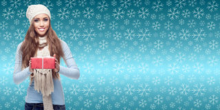 Happy young woman holding gift over winter background Royalty Free Stock Images